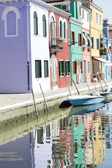 イタリア、ヴェネツィア、ブラーノ島のカラフルな家とボートの運河