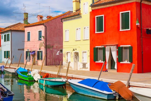 Colorful houses and boats in burano island with cloudy blue sky near venice, italy,