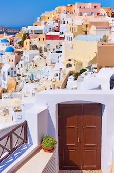 화창한 여름날 그리스 산토리니 섬에 있는 이아(oia) 마을의 다채로운 주택. 그리스 도시 풍경