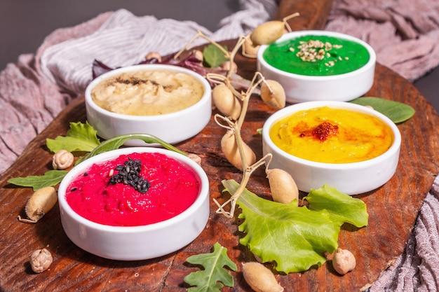 다채로운 후무스 그릇, 건강한 비건 딥. 전통적인 중동 음식입니다. 사탕무, 시금치, 향기로운 향신료. 검은 돌 콘크리트 배경, 가까이