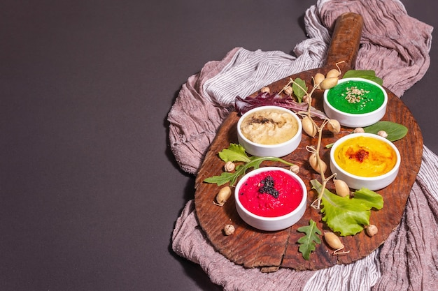 다채로운 후무스 그릇, 건강한 비건 딥. 전통적인 중동 음식입니다. 사탕무, 시금치, 향기로운 향신료. 검은 돌 콘크리트 배경, 복사 공간