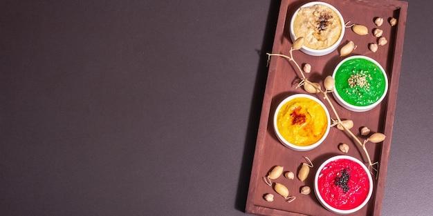 다채로운 후무스 그릇, 건강한 비건 딥. 전통적인 중동 음식입니다. 사탕무, 시금치, 향기로운 향신료. 검은 돌 콘크리트 배경, 평면도, 배너