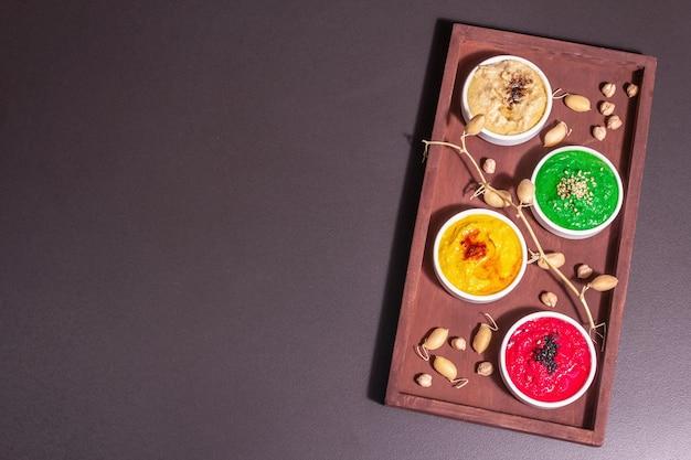 다채로운 후무스 그릇, 건강한 비건 딥. 전통적인 중동 음식입니다. 사탕무, 시금치, 향기로운 향신료. 검은 돌 콘크리트 배경, 상위 뷰