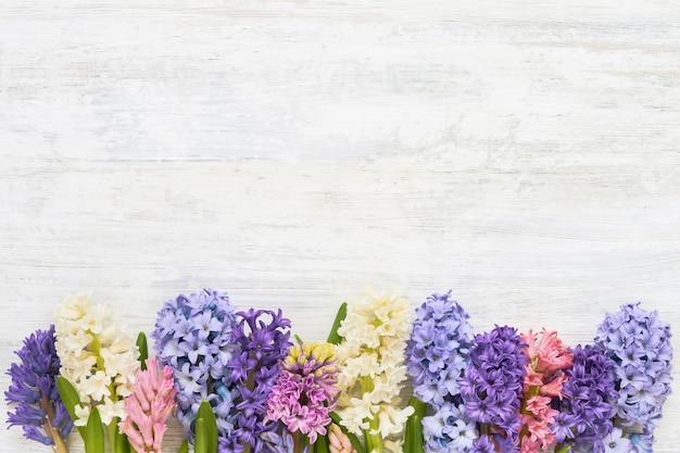 Красочная граница цветов гиацинта на белом деревянном столе. вид сверху, копия пространства.