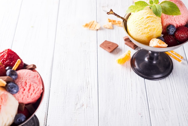 Colorful ice cream scoops and flavours with berries, chocolate and mint on wooden background