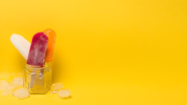 Colorful ice lolly in jar near ice