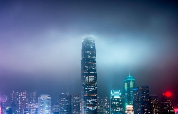 香港のフェスティバルで霧の上のカラフルな照らされた超高層ビル