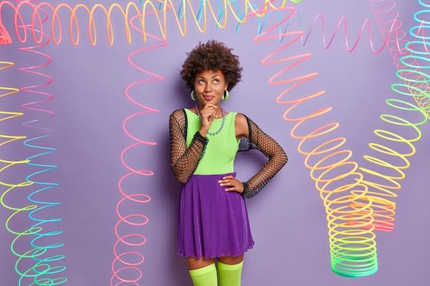 예쁜 사려 깊은 여자의 다채로운 이미지는 턱을 잡고 꿈꾸는 표정으로 위를 보며 녹색 셔츠, 치마 및 메쉬 케이프를 착용합니다.