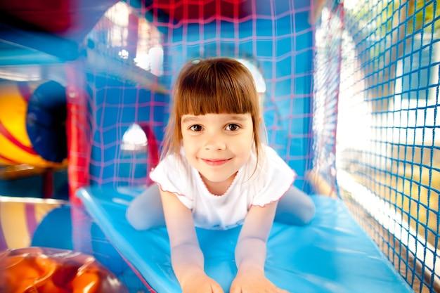 갈색 머리를 가진 소녀가 웃고 파란색 표면에 누워있는 다채로운 inflatables 놀이터