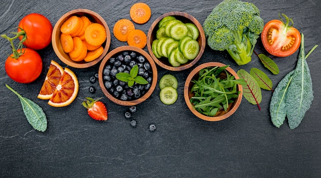 Colorful ingredients for healthy smoothies and juices on dark stone