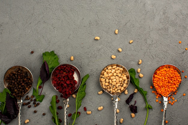 Colorful ingredients spices and raw multicolored beans on a light background