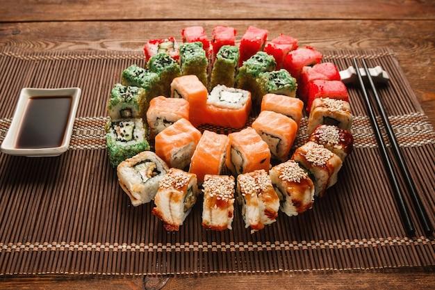 Красочные японские суши, искусство еды. аппетитная красочная спираль очень вкусного набора рулонов урамаки служила на коричневой соломенной циновке, крупном плане. фото меню восточного роскошного ресторана.