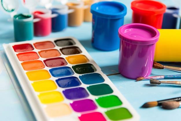 ガッシュと青色の背景に水彩絵の具でカラフルな瓶。