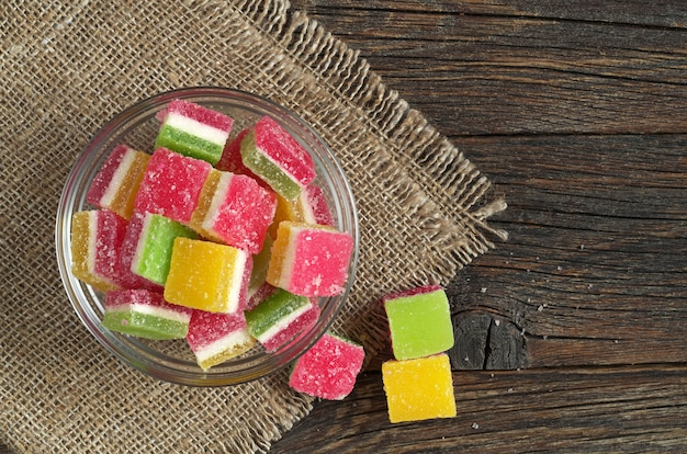 Colorful jelly candies in glass bowl on dark wooden background, top view