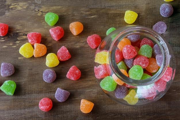 カラフルなゼリーシュガーキャンディーは、木製の菓子テーブルにアラビアガムの甘いものをガムします。上面図
