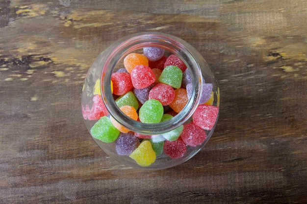 Colorful jelly sugar candies gum arabic sweet on wooden confectionery table. top view