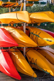 Colorful kayaks on the lake outdoor on a summer day.