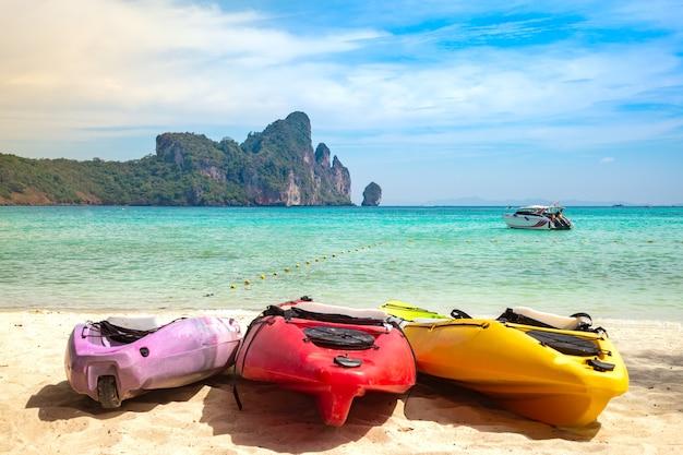 Разноцветные каяки на песке тропический пляж с моторной лодкой и скалами летний активный отдых