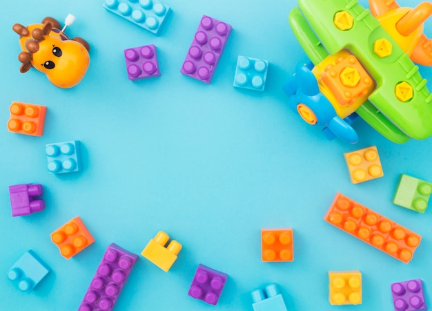 Colorful kids toys frame on blue background. top view for copy space
