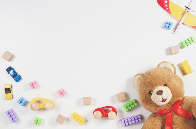 白いテーブルの上のカラフルな子供のおもちゃのフレーム。上面図。フラットレイ。