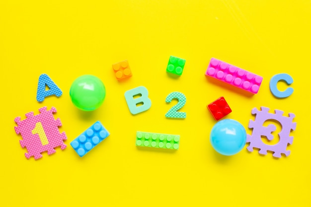 Colorful kids toys on yellow background