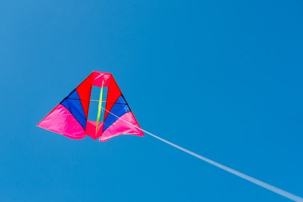 Colorful kite flying against blue sky background