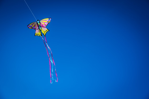 Colorful kite flying in the blue sky, negative space for copy.