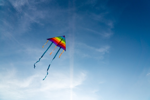 Colorful kite flying on the clear blue sky.