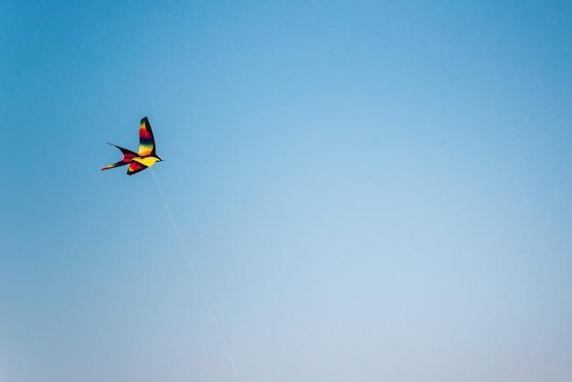 Красочный воздушный змей, летящий в голубом небе