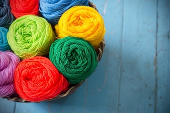 Colorful knitting in wooden basket