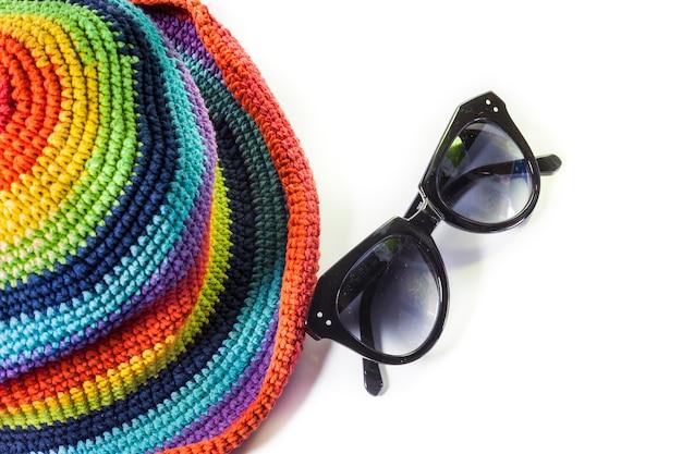 Красочные вязаные шерстяные шапки и солнцезащитные очки на белом