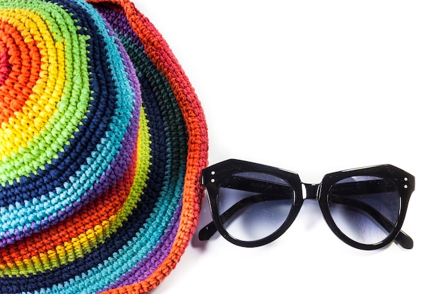 Colorful knitting wool hats and sunglasses on white