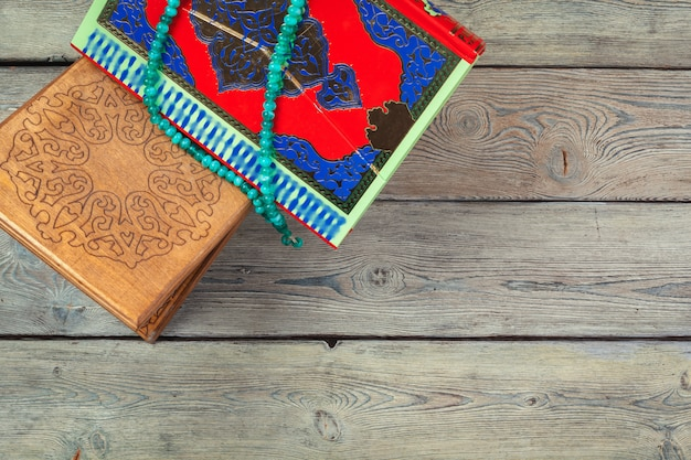 Colorful koran with rosary  on the wooden. holy book for muslims for ramadan concept