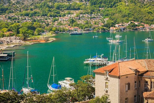 マリーナベイ、海、山、青い空にボートやヨットがあるカラフルな風景。モンテネグロのコトル湾の上面図
