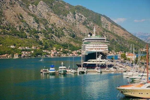 マリーナベイ、海、山、青い空にボート、クルーズ船、ヨットがあるカラフルな風景。モンテネグロのコトル湾の上面図