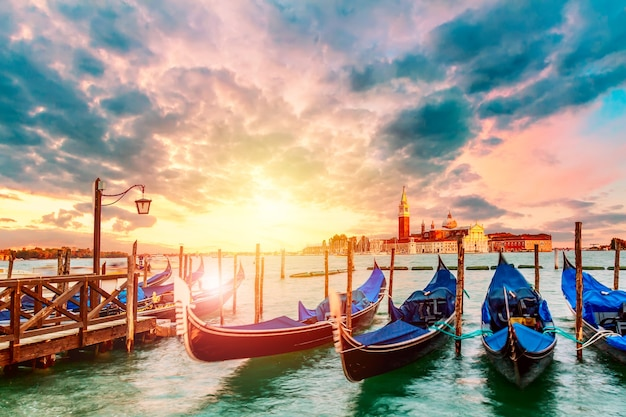 Colorful landscape with sunset sky and gondolas parked near piazza san marco in venice. church of san giorgio maggiore on background, italy. europe tourism concept.