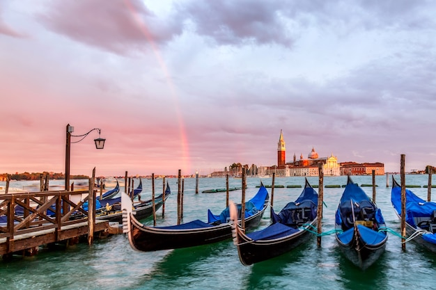 Colorful landscape with sunset sky, rainbow and gondolas parked near piazza san marco in venice. church of san giorgio maggiore on background, italy. europe tourism concept.