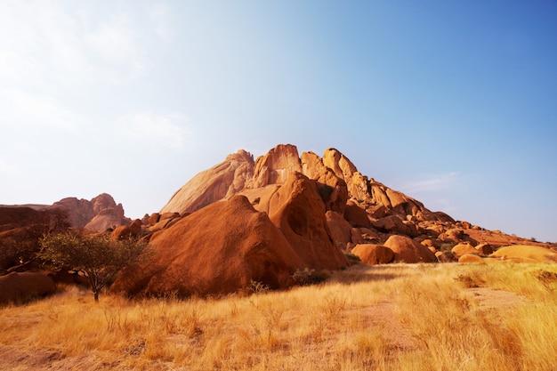 화창한 더운 날에 나미비아에서 산에 주황색 바위의 다채로운 풍경.