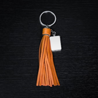 Colorful leather tassel key ring on black wooden background.