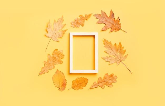 コピースペースと黄色の背景にカラフルな葉のフレーム。