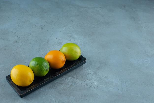 Красочные лимоны на доске, на мраморном фоне. фото высокого качества