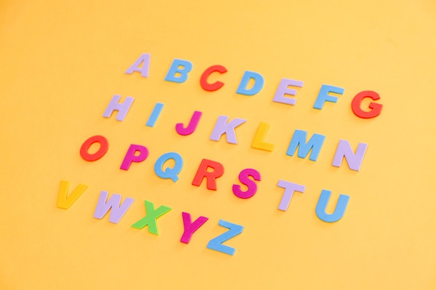 Colorful letters on yellow table.
