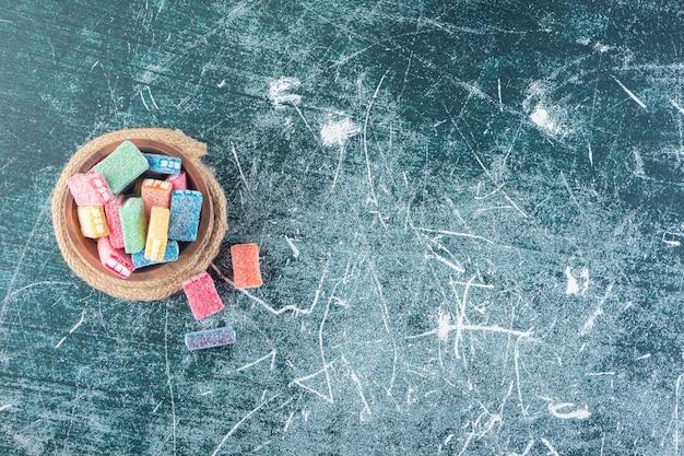 Liquirizia colorata in una ciotola profonda posta sul tavolo di pietra.