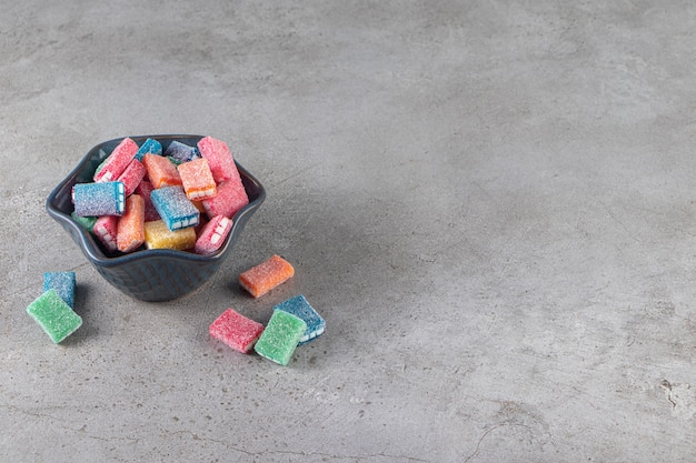 Colorful licorice in round black bowl placed on marble surface