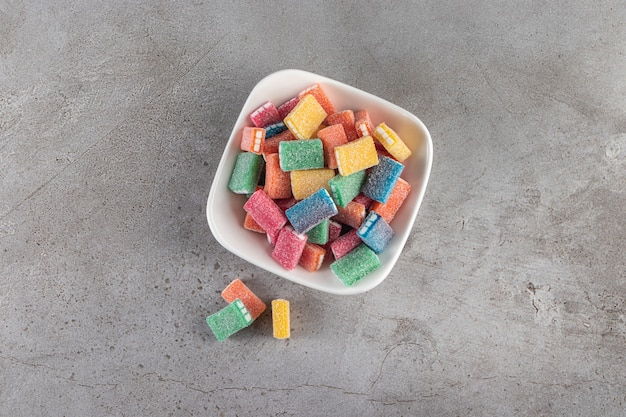 Colorful licorice in round white bowl placed on stone surface.