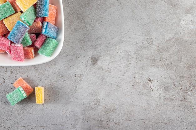 Liquirizia colorata in ciotola bianca rotonda posta sul tavolo di pietra.