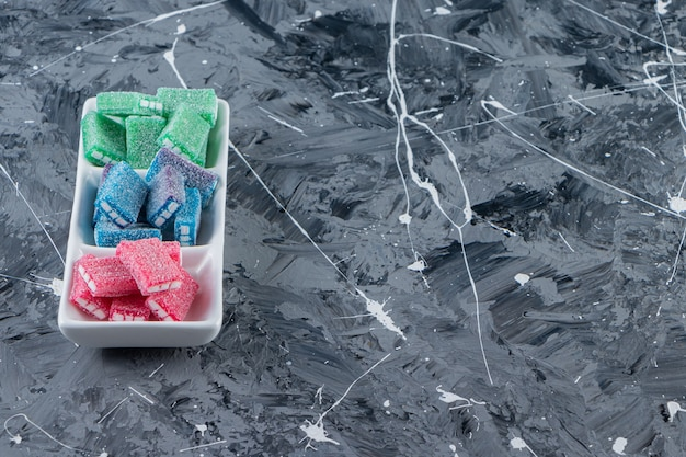 Colorful licorice in white board placed on marble surface