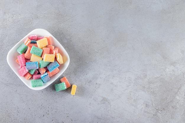 Liquirizia colorata in una ciotola profonda bianca posta sul tavolo di pietra.