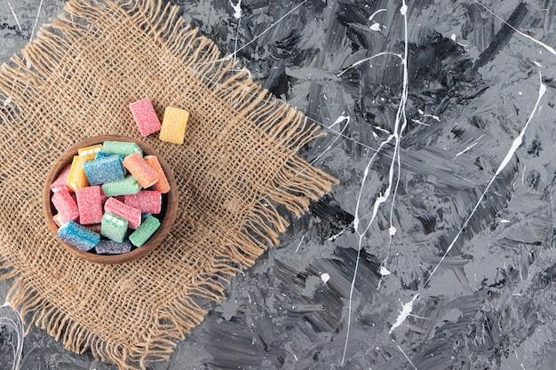 Liquirizia colorata in una ciotola di legno posta sulla superficie di tela di sacco.