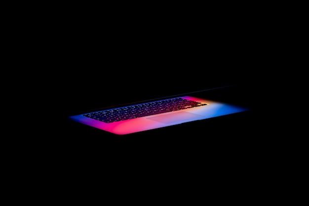 Luce colorata che esce dallo schermo di un laptop nell'oscurità